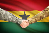 Men in uniform shaking hands with flag on background - Ghana — Stock Photo