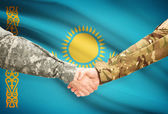 Men in uniform shaking hands with flag on background - Kazakhstan — Stock Photo