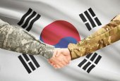 Men in uniform shaking hands with flag on background - South Korea — Stockfoto
