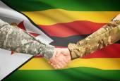 Men in uniform shaking hands with flag on background - Zimbabwe — Stock Photo