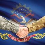 Military handshake and US state flag - North Dakota — Stock Photo #72521389