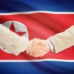 Businessmen handshake with flag on background - North Korea — Stock Photo #72711007