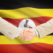 Businessmen handshake with flag on background - Uganda — Stock Photo #72711427