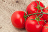 Bunch of red tomatoes on rustic wooden table - studio shot — Stock Photo