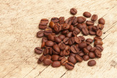 Coffee beans over old wooden table — Stock Photo