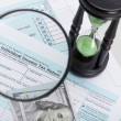 USA 1040 Tax Form with magnifying glass and hourglass - close up — Stock Photo #75958873