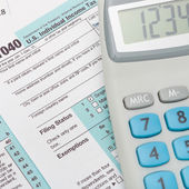 US 1040 Tax Form and calculator over it - close up — Stock Photo