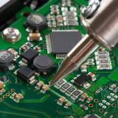 Soldering iron with microcircuit - close up — Stock Photo