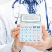 Doctor holding calculator in hands - health care concept - close up shot — Stock Photo