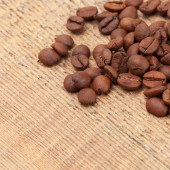 Coffee beans spread over wooden table - close up shot — Stock Photo