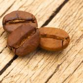 Three coffee beans on old table - close up shot — Stock Photo