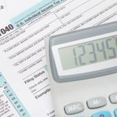 Calculator over US 1040 Tax Form - close up — Stock Photo