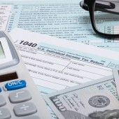 US 1040 Tax Form, calculator, glasses and dollars - close up — Stock Photo