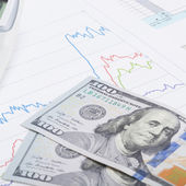 Stock market graph with calculator and 100 dollars banknote - close up — Stock Photo