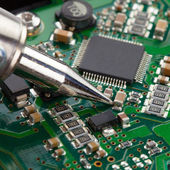 Soldering iron and microcircuit - close up — Stock Photo