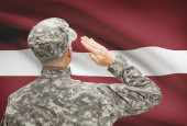 Soldier in hat facing national flag series - Latvia — Stock Photo