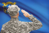 Soldier saluting to US state flag series - Nevada — Stock Photo