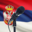 Microphone on stand with national flag on background - Serbia — Stock Photo #77535636