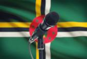Microphone on stand with national flag on background - Dominica — Stock Photo