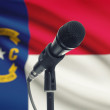 Microphone on stand with US state flag on background - North Carolina — Stock Photo #77582940
