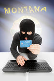 Hacker holding credit card with US state flag on background - Montana — Stock Photo