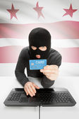 Hacker holding credit card with US state flag on background - District of Columbia — 图库照片