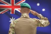 Dark-skinned soldier with flag on background - Australia — Stock Photo