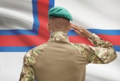 Dark-skinned soldier with flag on background - Faroe Islands — Stock Photo