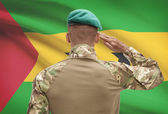 Dark-skinned soldier with flag on background - Sao Tome and Principe — Stock Photo