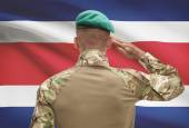 Dark-skinned soldier with flag on background - Costa Rica — Stock Photo