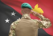 Dark-skinned soldier with flag on background - Papua New Guinea — Stock Photo