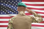 Dark-skinned soldier with flag on background - United States — Stock Photo