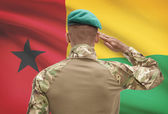 Dark-skinned soldier with flag on background - Guinea-Bissau — Stock Photo