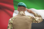 Dark-skinned soldier with flag on background - United Arab Emirates — Stock Photo