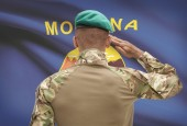 Dark-skinned soldier with US state flag on background - Montana — Stock Photo