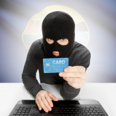 Hacker holding credit card with US state flag - Montana — Stock Photo