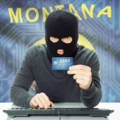 Hacker holding credit card and USA state flag - Montana — Stock Photo