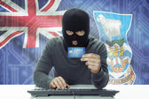 Dark-skinned hacker with flag on background holding credit card - Falkland Islands — Stock Photo