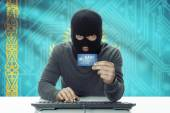 Dark-skinned hacker with flag on background holding credit card - Kazakhstan — Stock Photo
