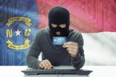 Dark-skinned hacker with USA states flag on background holding credit card - North Carolina — Foto de Stock
