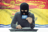Dark-skinned hacker with Canadian province flag on background holding credit card - New Brunswick — Stock Photo