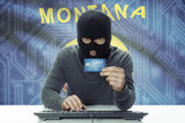 Dark-skinned hacker with USA states flag on background holding credit card - Montana — Stock Photo