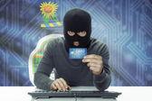 Dark-skinned hacker with USA states flag on background holding credit card - Kansas — Stock Photo