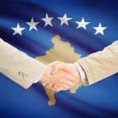 Zakenlieden handdruk met vlag op achtergrond - Kosovo — Stockfoto