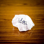 Wiriting idea word on crumpled  — Stock Photo