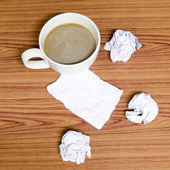 Coffee cup and crumpled — Stock Photo
