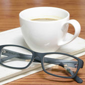 Coffee cup and notebook with glasses — ストック写真