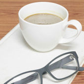 Coffee cup and notebook with glasses — Stock Photo