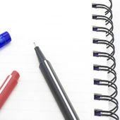 Black red and blue pen with notebook isolated on white — Stock Photo