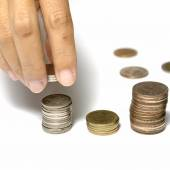 Hand putting stack of coins — Stock Photo